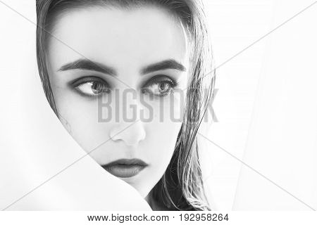 sensual beautiful female portrait at veil on white background with copy space, monochrome