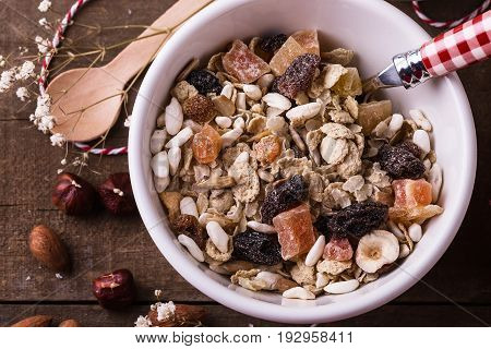 Macro view of bowl of healthy gluten free muesli with nuts and dried berry over rustic wooden background from above. Clean eating Healthy living Vegan Vegetarian Gluten free food concept