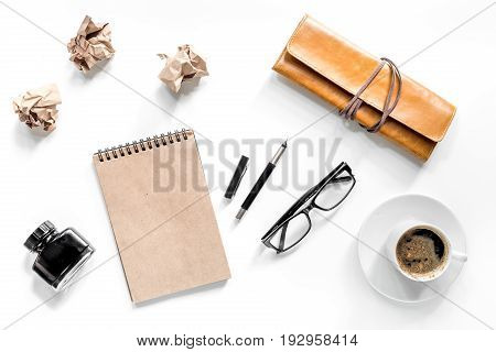 Writer acsessories. Vintage notebook, pen and crumpled paper on white background top view.