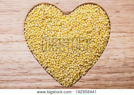 Dieting concept. Millet groats heart shaped on wooden surface. Healthy food help lower cholesterol.