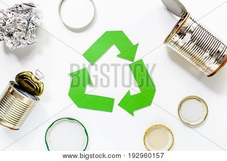 Paper recycle sign with plastic garbage on white background top view.