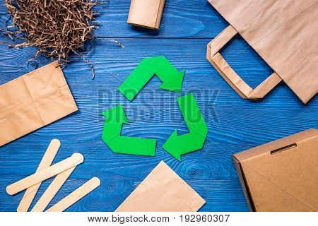 Paper recycle sign with paper and carton garbage on white background top view.