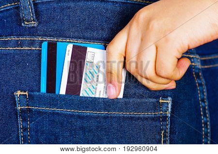 Woman hand putting a credit card and debit card inside of jeans back pocket.
