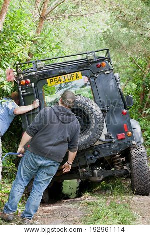 BEAULIEU HAMPSHIRE UNITED KINGDOM - JUNE 25 2017 Land Rover day with many varieties of Land Rovers this Land Rover has slipped off a dusty off road track in the woods and got stuck roof rack caught in trees.