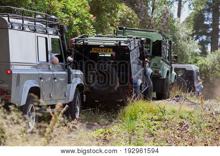 BEAULIEU HAMPSHIRE UNITED KINGDOM - JUNE 25 2017 Land Rover day with many varieties of Land Rovers these are driving in a row on a dusty off road track in the woods.