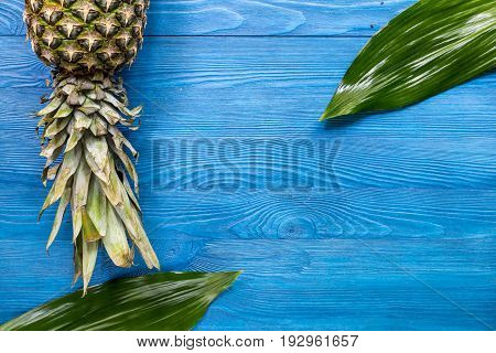 Pineapple and leaves on blue wooden desk background top view.