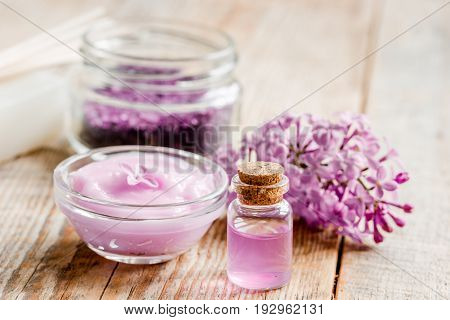 spa cosmetic set with lilac flowers on wooden desk background