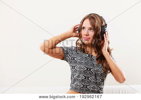 People leisure relax concept. Young woman in big headphones listening music mp3 relaxing at home on sofa