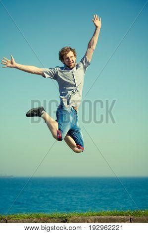 Carefree Man Jumping By Sea Ocean Water.
