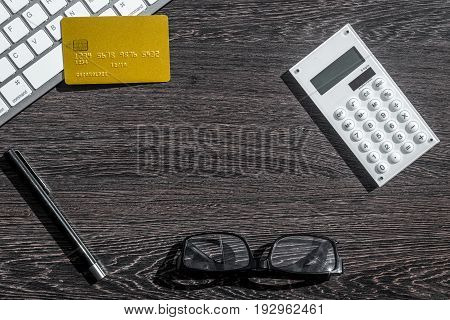 business purchasing with credit cards, keyboard and glasses on banker work desk dark background top view space for text