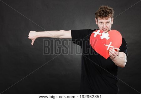 Very Sad Young Man Holding Broken Heart