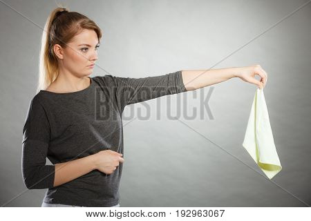Household duties concept. Young disgust girl holding cleaning cloth rag doing domestic chores. Unhappy housewife.