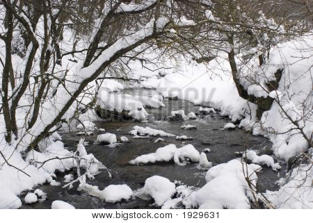 Flowing Water With Snow And Forest Trees