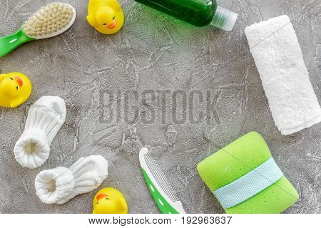 bath cosmetic set for kids, towel and toys on gray stone background top view space for text