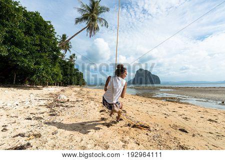 EL NIDO, PALAWAN, PHILIPPINES - MARCH 29, 2017: Girl with glasses playing at swing at Las Cabanas Beach