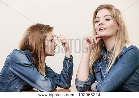 Two women having argue mocking up being mad at each other. Female telling off ignorance coversation concept.