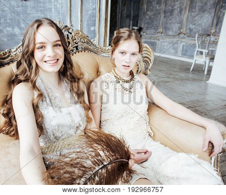 two pretty twin sisters blond curly hairstyles in luxury house interior together, rich young people concept close up