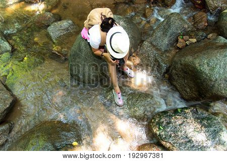 Asian women photography take a photo of waterfall in deep forest in Thailand