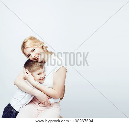 young modern blond mother with cute son together happy smiling family posing cheerful on white background, lifestyle people concept, sister and brother friends close up