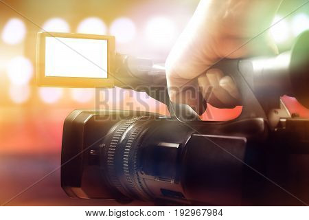 hand of cameraman holding professional video camcorder in studio with blurred background