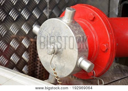 Firefighting equipment on red fire truck. Water hydrant closeup photo with selective focus
