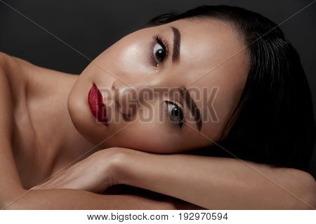 Face of gorgeous Chinese woman leaning on her arm