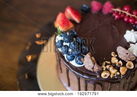 Delicious chocolate cake with fruits on table.