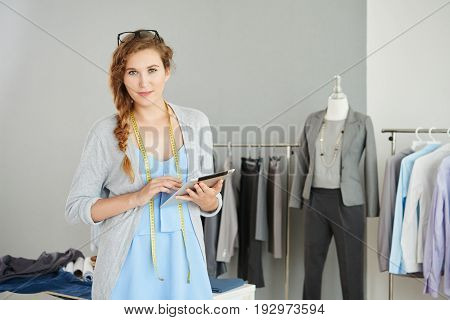 Portrait of pretty young dressmaker with digital tablet looking at camera