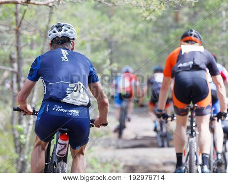 STOCKHOLM SWEDEN - JUNE 11 2017: Rear view of group of mountain bike cyclists in the forest at Lida Loop Mountain bike Race. June 11 2017 in Stockholm Sweden