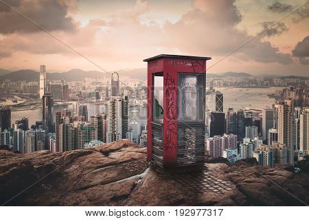 phone booth isolated on a rocks hill in front of the city