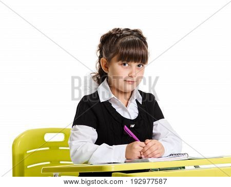 Smart schoolgirl sitting at the desk and writing in exersice book