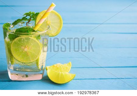 Lemonade in glass put on light blue wood table. Lemon or lime and mint leaf in sparkling water or soda. Lemon or lime mojito make fresh and cool for summer. Lemonade or lime juice with copy space.