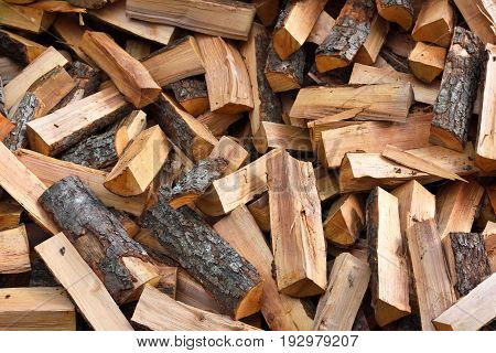 Firewood background - chopped firewood on a stack. Dry chopped firewood logs in a pile.