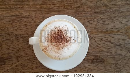 Top view white cup of mocha coffee on wooden background