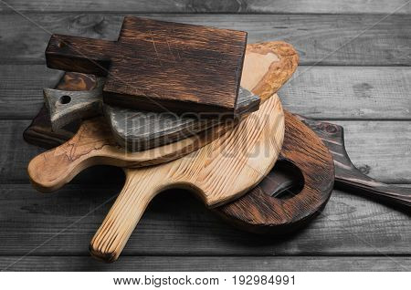Cutting chopping different old wooden boards. Cutting boards of different shapes stacked on a gray wooden background.