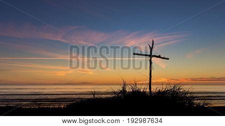 Cross on a sand dune on a beach as the sunsets.
