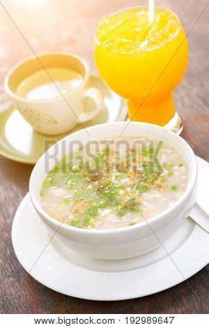 Boiled rice pork or mush with orange juice and hot coffee on wood table with sunlight.