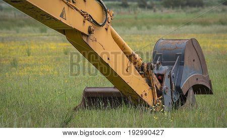 Close up image of the hydraulic arm of an excavator digger unused on an agricultural field