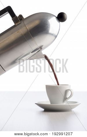 pouring coffee from coffeepot into white coffee cup on white table.