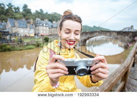 Young woman in yellow raincoat traveling with backpack and photo camera in Dinan village at Brittany region in France