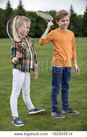 Adorable Smiling Children Holding Badminton Racquets While Standing On Green Grass