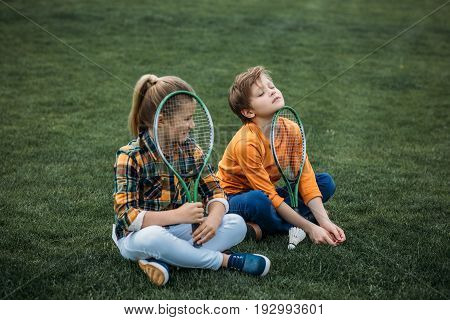 Tired Brother And Sister With Badminton Racquets Sitting On Green Field