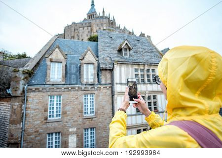 Young woman in yellow raincoat photographing buildings visiting a famous Mont Saint Michel island in France
