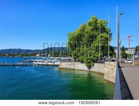 Zurich, Switzerland - 18 June, 2017: embankment of Lake Zurich in the city of Zurich, people on piers, hills in the background, as seen from Quaibrucke bridge. Lake Zurich is a lake in Switzerland, extending southeast of the city of Zurich.