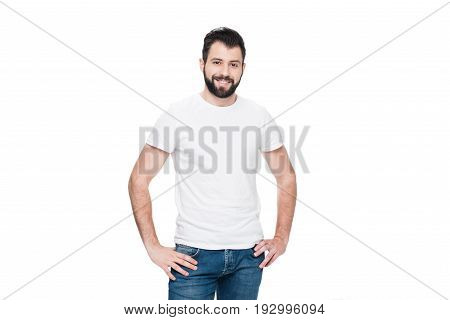 Bearded Young Man In White T-shirt Standing With Hands On Hips And Smiling At Camera
