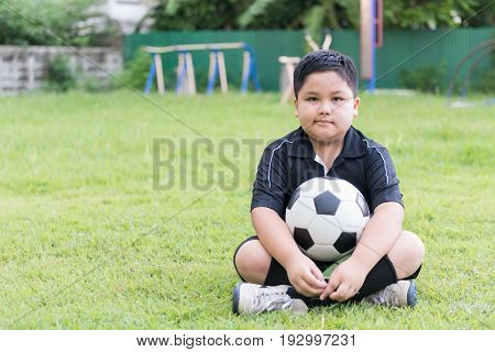 Sitting Obese Fat Boy  Soccer Player With Football