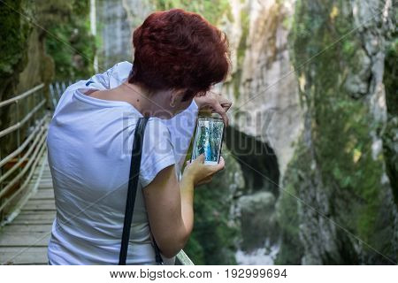 ANNECY FRANCE GORGES DU FIER - JUNE 17 2017: Undefined woman do mobile photo of beautiful Gorges du Fier french canyon near Annecy