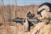 airsoft player in NATO uniform with rifle in ambush close up picture poster