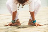 closeup of barefoot woman practice yoga outdoor by lake wearing white clothes and lot of anklets and toe ring lower body poster