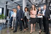 Full Length Business People Team Walking In Modern Office, Confident Businessmen And Businesswomen In Suits Diverse With Mature Leader In Foreground poster